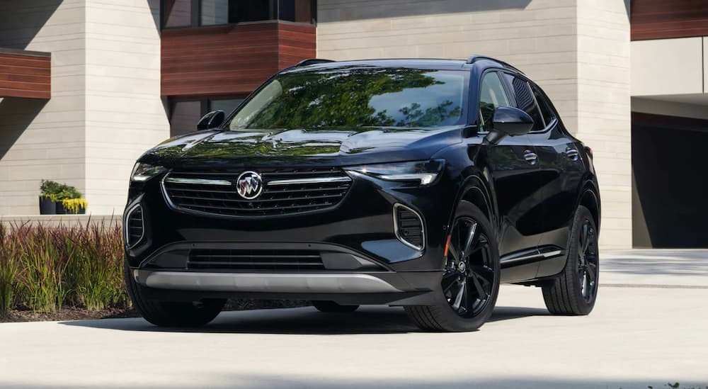 A black 2022 Buick Envision is shown from the front parked in front of a modern house.